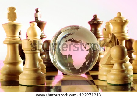 Globe and chess pieces - stock photo