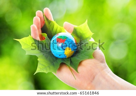 globe and leaf in hands for environmental conservation - stock photo