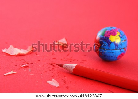 Globe and pencil on red background - stock photo