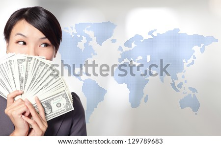 Globe business concept - happy business woman with earned dollar bills us money with world map background, asian beauty model - stock photo