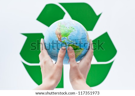 globe in hands on the recycling sign - stock photo