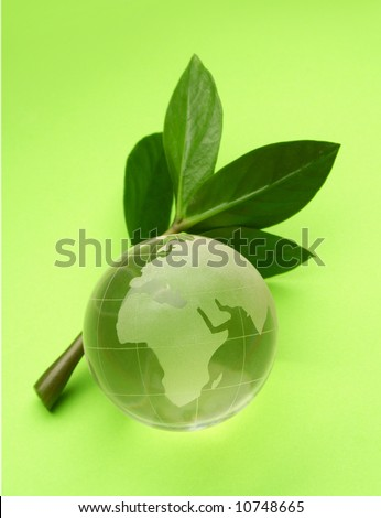 globe isolated on green background with small plant. Concept suitable for environment protection themes. - stock photo
