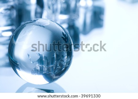 Globe made of glass in blue ambient light. - stock photo