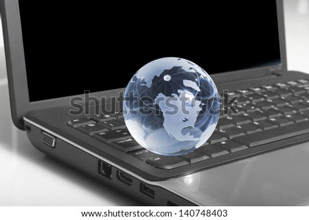 Globe on a keyboard laptop - stock photo