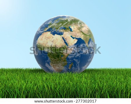 Globe on grass Elements of this image furnished by NASA - stock photo