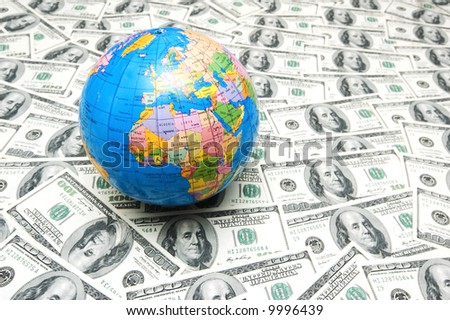Globe over many american dollar bank notes - stock photo