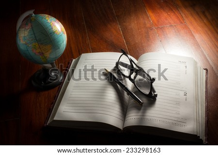 Globe with eyeglasses,pen and plan book - stock photo
