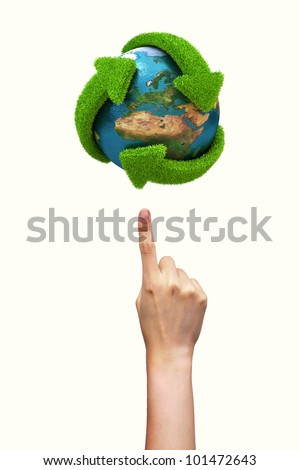 Globe with green arrows covered with grass presented on female finger. Elements of this image furnished by NASA - stock photo