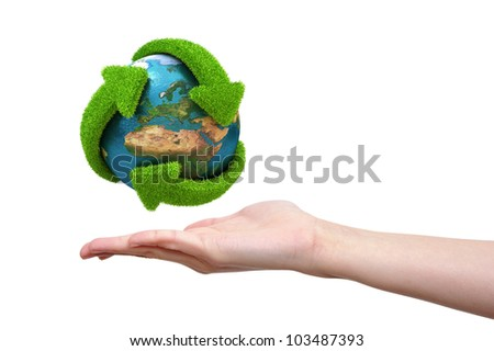 Globe with green arrows covered with grass presented on female hand. Elements of this image furnished by NASA - stock photo