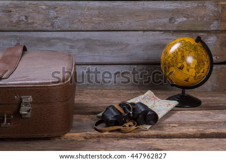 Globe with map and binoculars. Brown suitcase and black binoculars. Captain's things on wooden shelf. Discover the world. - stock photo