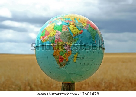 globe with world map in a real background with cereal field and blue sky - stock photo