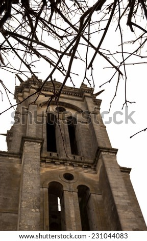 Gloomy ancient church through the bare tree twigs. (Senlis, France). Selective focus on the twigs. - stock photo