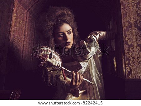 Gloomy duchess with mask. Vogue style vintage portrait in luxury interior. - stock photo