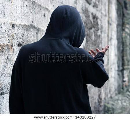 Gloomy man in a hood on the street. - stock photo