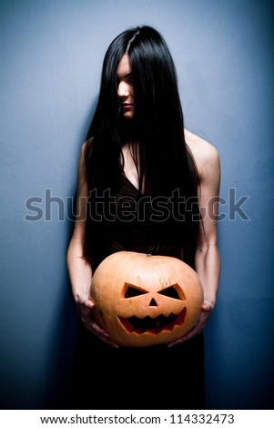 Gloomy young woman holding a large orange pumpkin carved for Halloween celebration. Dark background. - stock photo