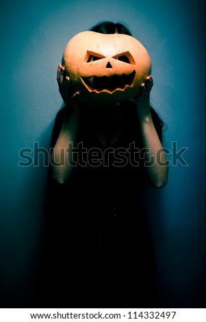Gloomy young woman holding a large orange pumpkin for Halloween in front of her face. Dark background - stock photo