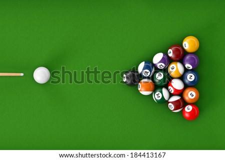 Glossy billiard balls set on a green billiards table - stock photo