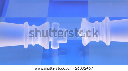 Glossy king and queen chess coins on blue background - stock photo