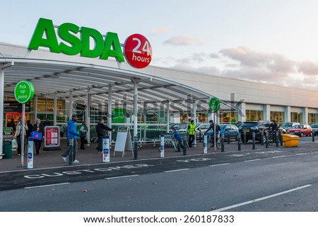 GLOUCESTER, UK - DECEMBER 07: unidentified people passing by Asda supermarket on December 07, 2011 in Gloucester, UK. Asda is the UK's second-largest chain by market share, with over 175,000 employees - stock photo