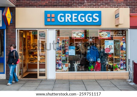 GLOUCESTER, UK - DECEMBER 04: unidentified woman leaving Greggs bakery shop on December 04, 2011 in Gloucester, UK. Founded in 1939, Greggs is the largest bakery chain in the UK with 1,671 outlets. - stock photo