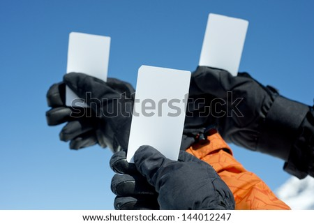 Gloved hands holding lift pass against blue sky. Concept to illustrate ski admission fee - stock photo