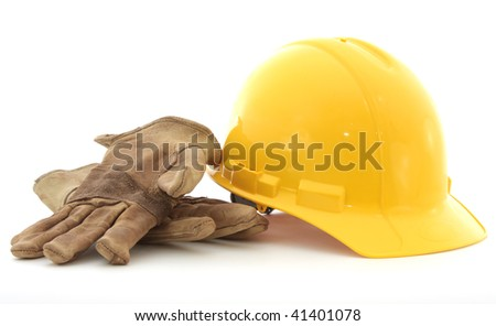 Gloves and a hardhat against a white background. - stock photo