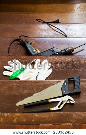 gloves, saw, wrench, electric drill, screwdriver on old wood staircase / repair, renovation , building and home interior concept - stock photo