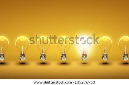 glow among other light bulb on a orange background - stock photo