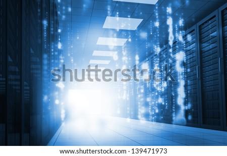 Glowing blue matrix falling in data center - stock photo