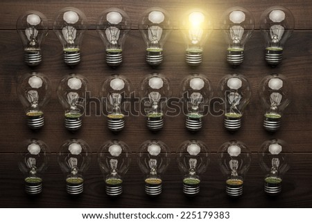 glowing bulb uniqueness concept on brown wooden table - stock photo