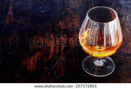 Glowing cognac or brandy in an elegant snifter glass on an old dark wooden bar counter with copyspace, high angle view - stock photo