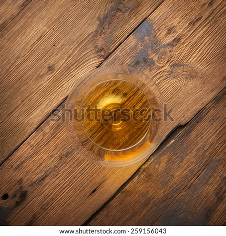 Glowing cognac or brandy in an elegant snifter glass on an old dark wooden bar counter with copyspace. top vive - stock photo