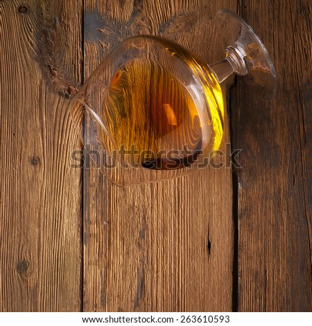 Glowing cognac or brandy in an elegant snifter glass on an old dark wooden bar counter with copyspace - stock photo