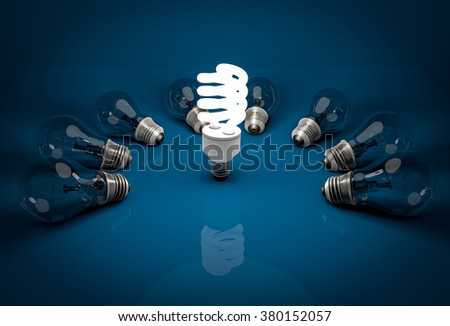 Glowing energy saving bulb among lying dark incandescent bulbs  - stock photo