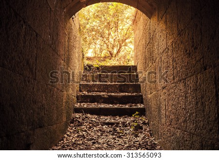 Glowing exit with stairs from dark abandoned concrete tunnel interior, warm tonal correction filter - stock photo