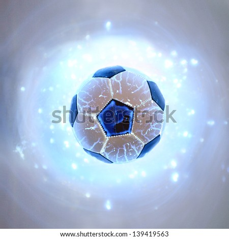 Glowing football ball on blue background - stock photo
