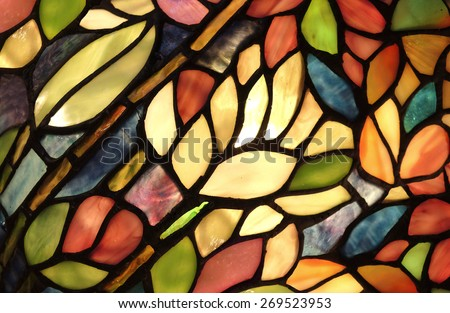 Glowing Glass Art. Backlit hand crafted glass art from church window with flowers and vivid colors. - stock photo