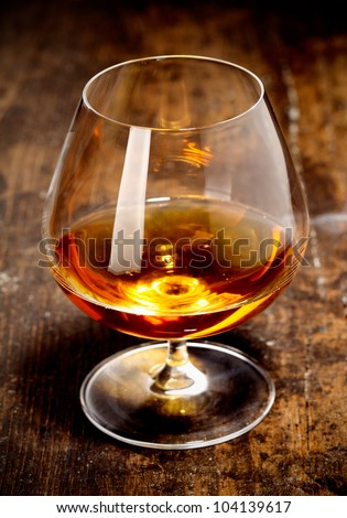 Glowing goblet of rich cognac on a wooden bar counter on a relaxing night out with friends - stock photo