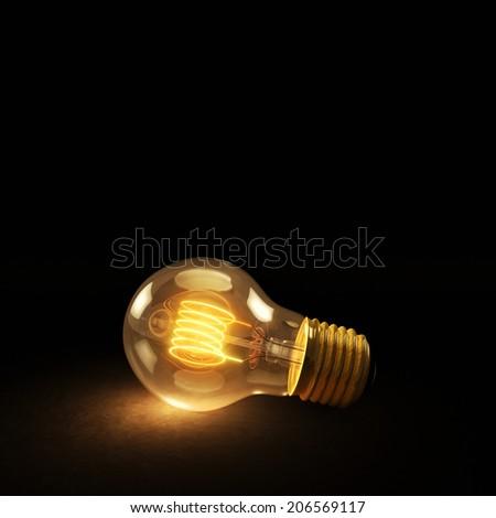 Glowing Incandescent Light Bulb Lying Sideways on a Dark Background - stock photo