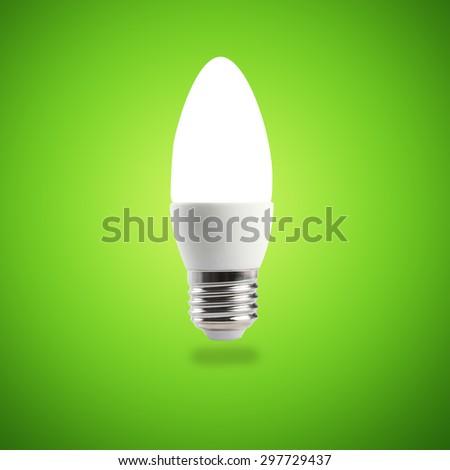 Glowing LED energy saving bulb on green background - stock photo