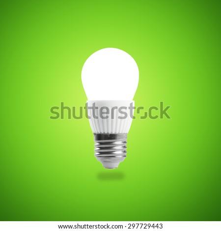 Glowing LED energy saving bulb on green background. - stock photo