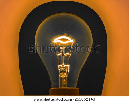 glowing light bulb by electrical current in metal filament - stock photo
