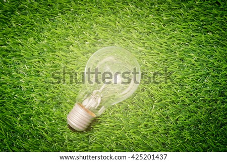 Glowing light bulb hanging above grass symbol of ecological energy - stock photo