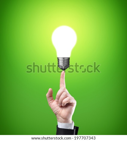 Glowing light bulb on tip of finger on businessman - stock photo