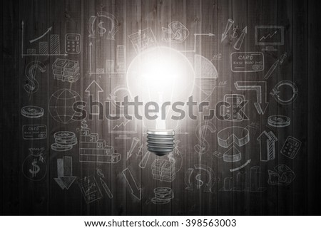 Glowing light bulb on wooden wall with drawing charts and graphs about business success strategy plan - stock photo