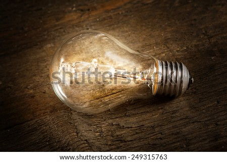 Glowing lightbulb on wooden background - stock photo