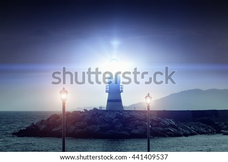 Glowing lighthouse and two lanterns on the background of stones and sea at dusk - stock photo