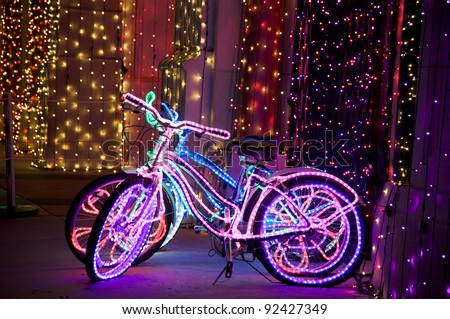 Glowing psychedelic bikes with multicolored Christmas lights - stock photo