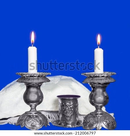 Glowing Sabbath candles on blue background. Selective focus closeup on two wax candles in antique silver candlesticks. Covered challah and kiddush cup with red wine in background. Square composition.  - stock photo