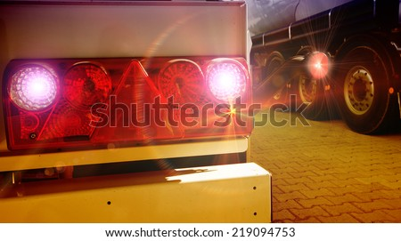 Glowing tail lights of parked truck in evening - stock photo